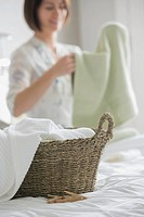 Woman folding towels in bedroom with rattan basket in foreground