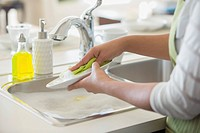 Woman washing white plate in sink