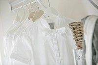 Close_up of white blouse and shirts hanging in closet