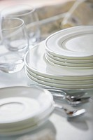 Stacked fine china dishes with silver edge on counter