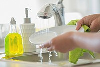 Woman rinsing white plate in kitchen sink.