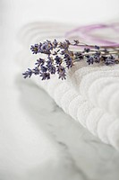 Close_up of lavender sprig on white towels