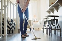 Mid_adult woman dusting floors in modern home
