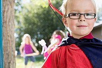 Portrait of six year old boy dressed in cape with bow and arrow