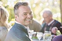 Middle-aged man smiling at family outdoor dinner (thumbnail)
