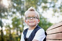 Portrait of six year old blond boy sitting on bench outdoors