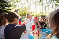 Kids handing out plastic glasses at the kids picnic table
