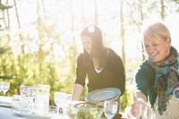 Mother and teenage daughter setting table outdoors