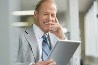 Middle_aged business man using pc tablet in office