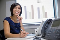 Asian businesswoman smiling in meeting room
