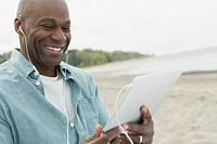 Middle_aged African American man listening to music on pc tablet