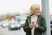 Mature woman texting on smartphone on city sidewalk