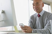 Mature Asian businessman texting on smartphone.