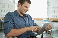 Attractive, mid_adult man using pc tablet in office
