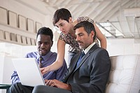 Three businesspeople looking down at laptop computer together