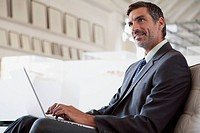 Middle_aged businessman with laptop at office