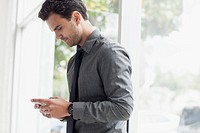 Young businessman texting on smartphone