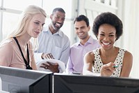 Four coworkers having a laugh as they look at desktop computer