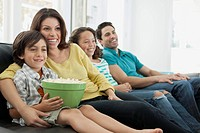 Family of four enjoying popcorn on movie night