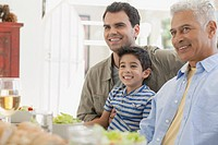 Young boy with his dad and grandpa at dinner table.