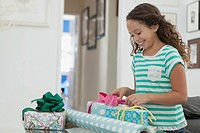 Young girl smiling as she adds ribbons to presents