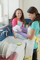 Mother and daughter laughing while doing dishes