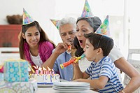 Family blowing out candles with noisemakers