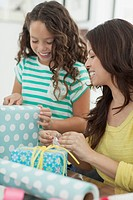 Mother and young daughter wrapping gifts