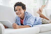 Preteen boy on sofa with pc tablet.