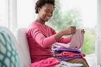 Mid_adult woman folding clean laundry
