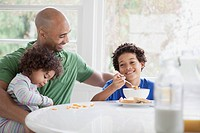 Father and sons having cereal for breakfast