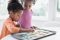 Young sisters decorating cookies together.