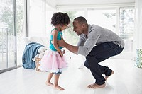 Dad and young daughter dancing in sunroom