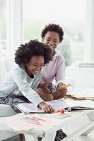 Mother and daughter working on scrapbook together