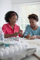 Mother and daughter creating a shopping list from recipe