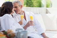 Couple in robes drinking orange juice