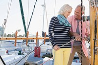 Senior couple tying up sailboat