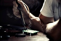 Hand of computer engineer doing repair of circuit board