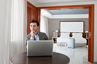 Businessman using laptop in hotel room