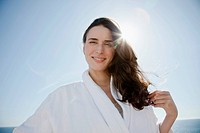 Portrait of woman in bathrobe against blue sky