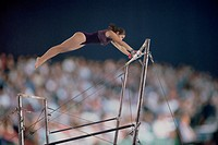 Female gymnast competing on the uneven bars in front of a large crowd