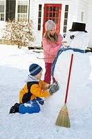 Two children building a snowman