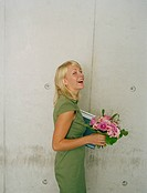 blonde woman holding a bunch of flowers and smiling