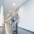 Businessman skateboarding in office building corridor