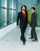 Two Businessmen Passing Briefcase in Hallway