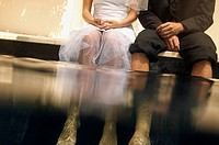 Bride and bridegroom sitting with feet in water