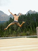 Muddy young man jumping into a lake