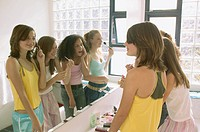 Girls applying makeup in bathroom mirror