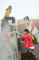 Teenagers spray_painting a concrete barrier