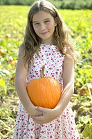 Contended girl holding pumpkin in field
